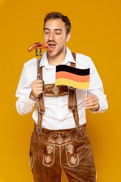 Homme avec saucisse allemande et drapeau Photo gratuit