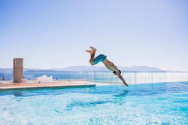 Homme sautant dans la piscine Photo gratuit