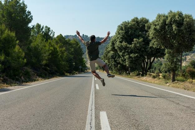 Homme sautant sur la route vide. globe-trotter Photo Premium