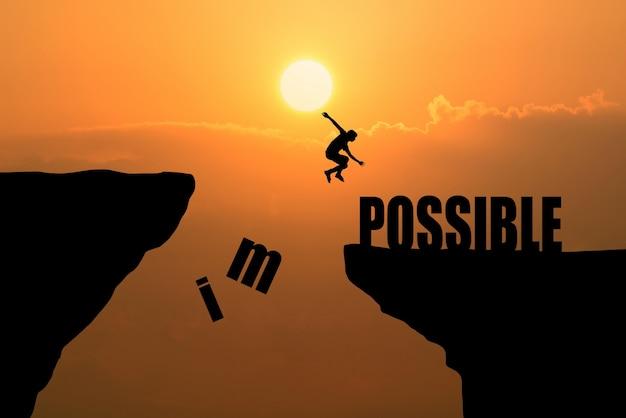 L'homme saute sur impossible ou possible sur une falaise sur le fond du coucher du soleil, idée de concept d'entreprise Photo gratuit