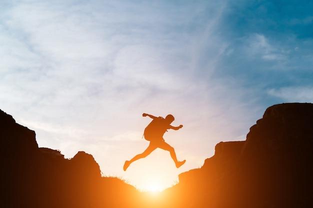 Un homme saute à travers des brèches entre des collines Photo gratuit