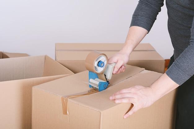 Homme scellant une boîte en carton d'expédition Photo Premium