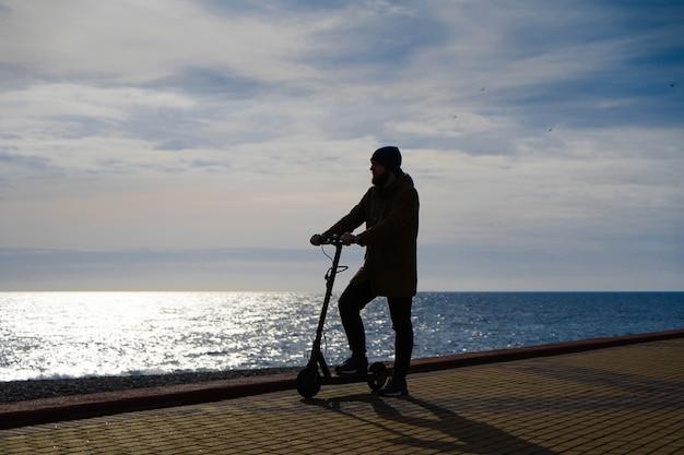 Homme sur un scooter au coucher du soleil, silhouette, espace libre Photo Premium