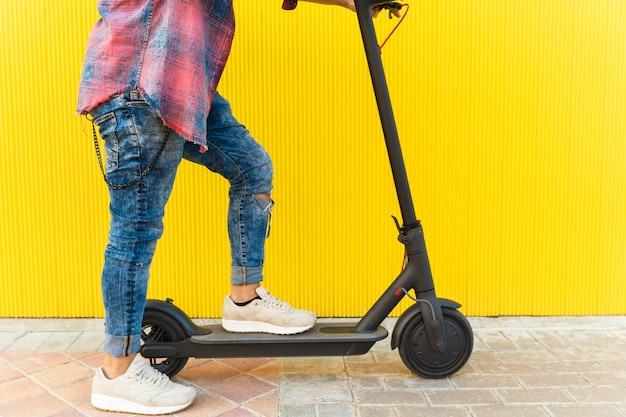 Homme sur un scooter électrique sur fond jaune. Photo Premium