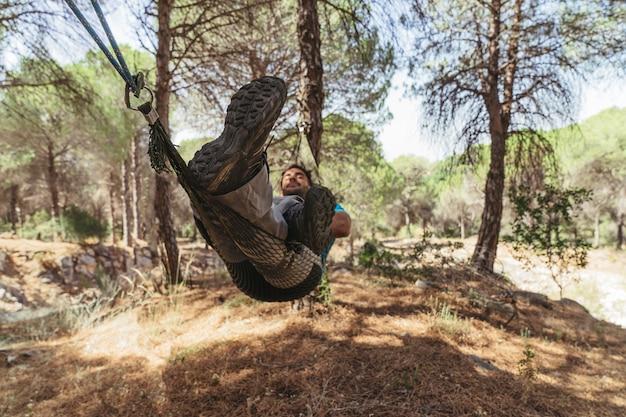 L'homme se détend dans un hamac dans la forêt Photo gratuit