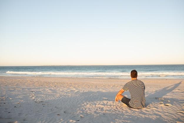 Homme se détendre sur la plage Photo gratuit