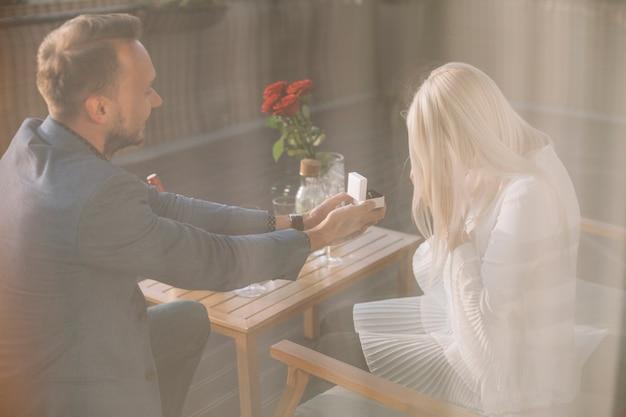 Un homme se propose d'offrir une bague de fiançailles au restaurant Photo gratuit