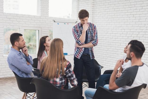 L'homme se tient en cercle de personnes au cours d'une séance de thérapie de groupe. Photo Premium