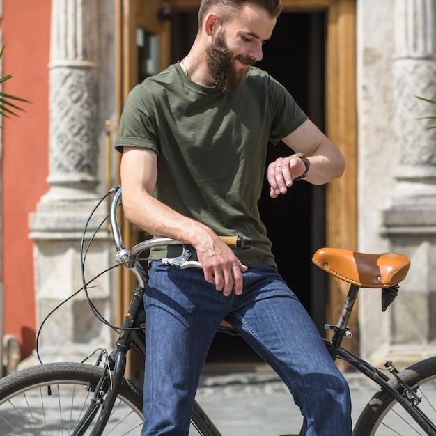 Homme, séance, vélo, regarder, temps, montre bracelet Photo gratuit