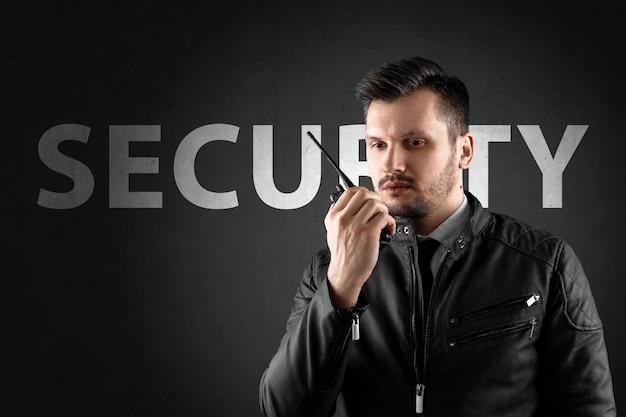 L'homme, la sécurité, tient un talkie-walkie Photo Premium