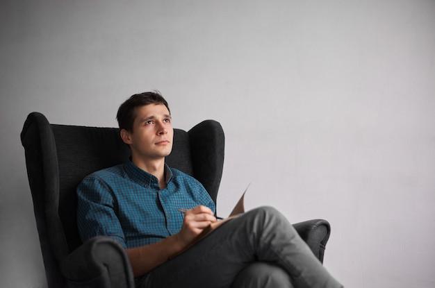 Homme Séduisant En Chemise Bleue à Carreaux écrivant De Nouvelles Idées Dans Un Cahier Avec Un Stylo Photo gratuit
