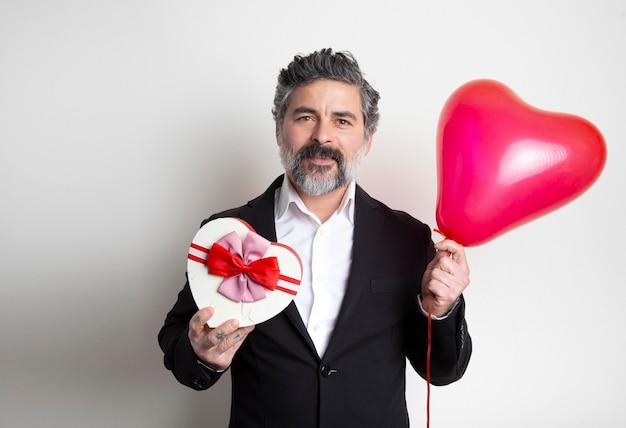 Homme Séduisant En Costume Tenant Une Boîte Et Un Ballon Rouge En Forme De Coeur. Photo Premium