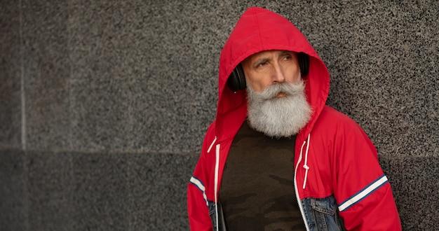 Un Homme Senior Barbu Branché, écouter De La Musique En Plein Air. Homme Mature De Mode. Photo Premium