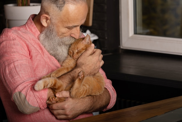 Homme Senior Barbu Tenant Un Chat Mignon à La Maison. Photo Premium