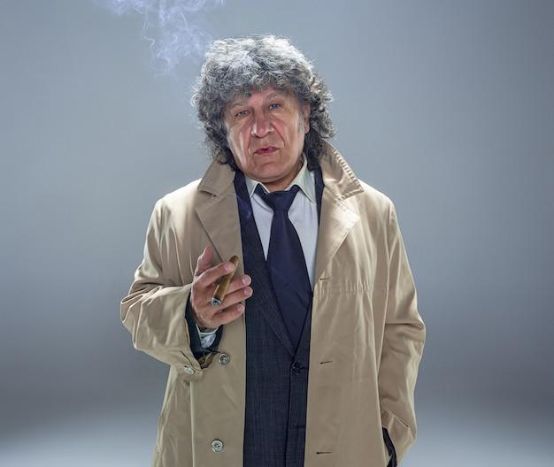 L'homme Senior Avec Cigare Comme Détective Ou Patron De La Mafia Sur L'espace Studio Gris Photo gratuit