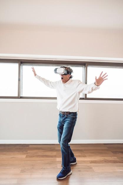 Homme senior étonné touchant dans les airs pendant l'expérience vr Photo gratuit