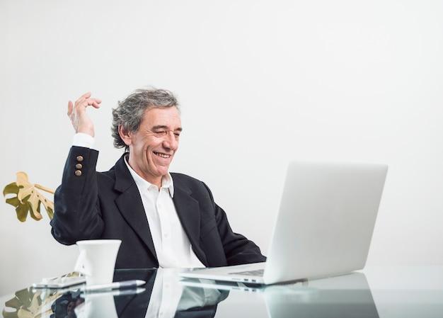 Homme senior excité souriant, assis sur le lieu de travail à la recherche d'un ordinateur portable Photo gratuit