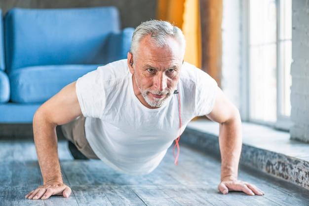 Homme senior faisant des pompes à la maison Photo gratuit
