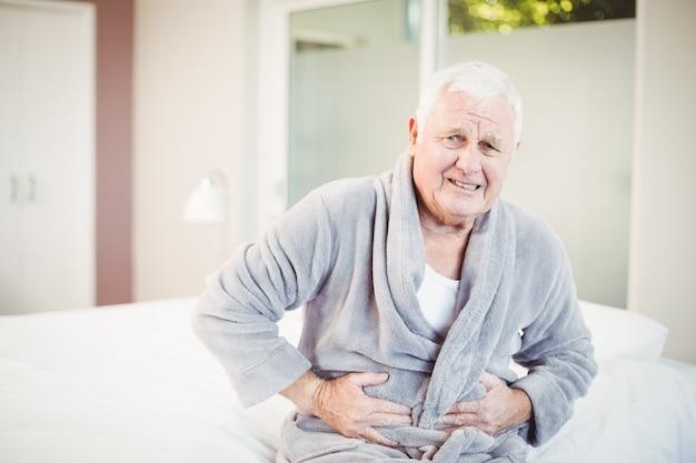 Homme senior fronçant les sourcils avec maux d'estomac Photo Premium