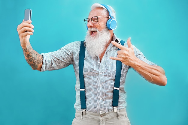 Homme Senior Hipster Utilisant L'application Smartphone Pour Créer Une Liste De Lecture Avec De La Musique Rock Photo Premium