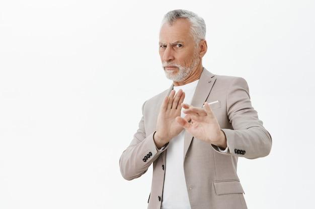 Homme Senior Mécontent Et Réticent Levant Les Mains Arrêter Le Geste, Rejeter L'offre, Fond Blanc Photo gratuit
