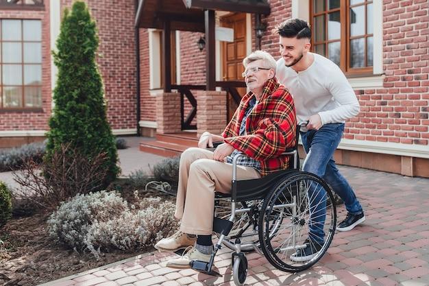 Un homme de seniot se lève sur une chaise roulante et son fils l'aide. près de la maison de retraite. Photo Premium