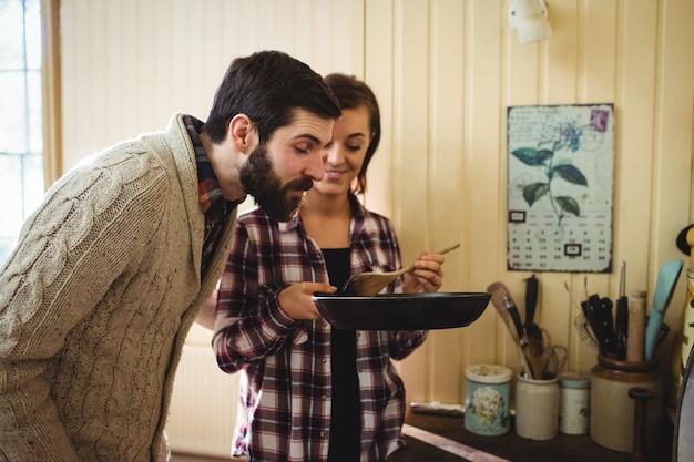 Homme sentant la nourriture préparée par une femme Photo gratuit