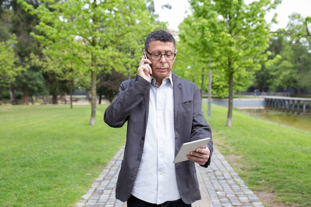 Homme sérieux à l'aide de tablette et parler au téléphone dans le parc Photo gratuit