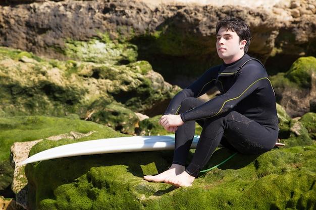 Homme sérieux assis sur des rochers moussus avec planche de surf Photo gratuit