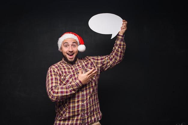 Homme Sérieux Drôle En Bonnet De Noël Rouge De Noël Détient Un Carton Blanc Vide Comme Blanc Ou Maquette Avec Espace De Copie Pour Le Texte. Fond Noir Photo Premium