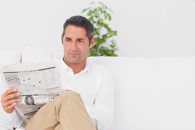 Homme sérieux lisant un journal dans le salon Photo Premium