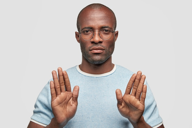 Un Homme Sérieux à La Peau Sombre Montre Un Geste D'arrêt Photo gratuit