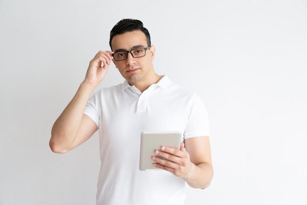 Homme sérieux tenant une tablette et ajustant des lunettes. Photo gratuit
