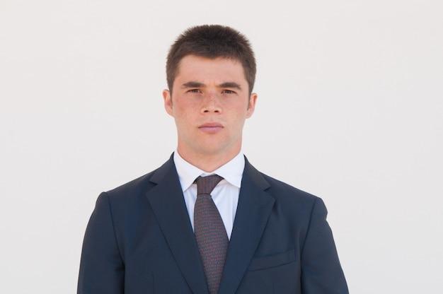 Homme sérieux en veste formelle et cravate debout pour la caméra Photo gratuit