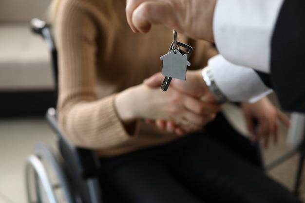 L'homme Serre La Main D'une Personne Handicapée, Clé De La Maison Photo Premium
