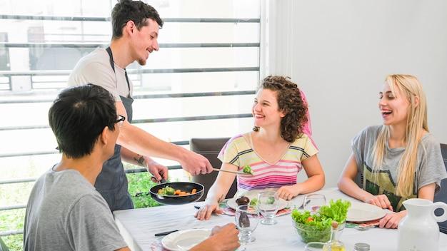 Homme servant des légumes cuits à ses amies à la maison Photo gratuit