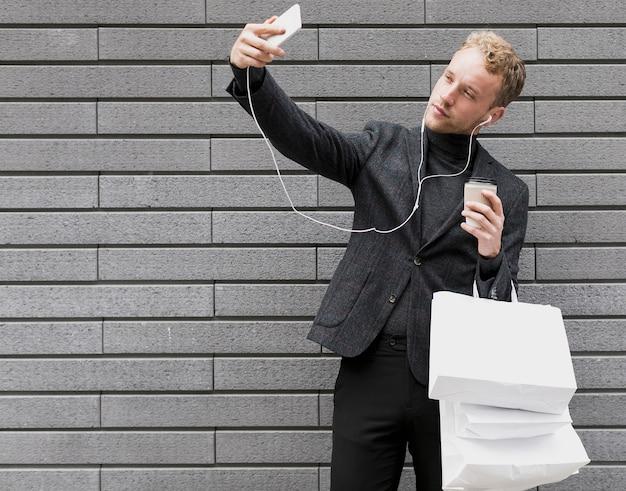 Homme seul avec des écouteurs prenant un selfie Photo gratuit