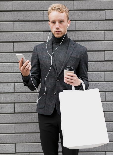 Homme seul avec des sacs à provisions et smartphone Photo gratuit