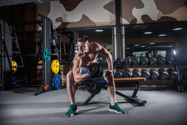 Homme sexy dans le gymnase avec des haltères. homme sportif avec de gros muscles Photo Premium