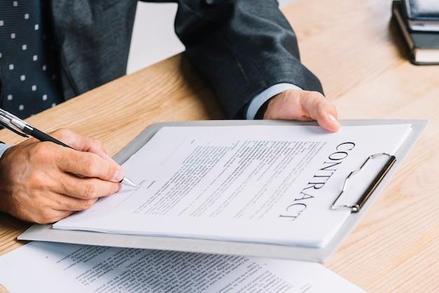 Un homme signant le papier contract attache sur le presse-papiers sur la table en bois Photo gratuit