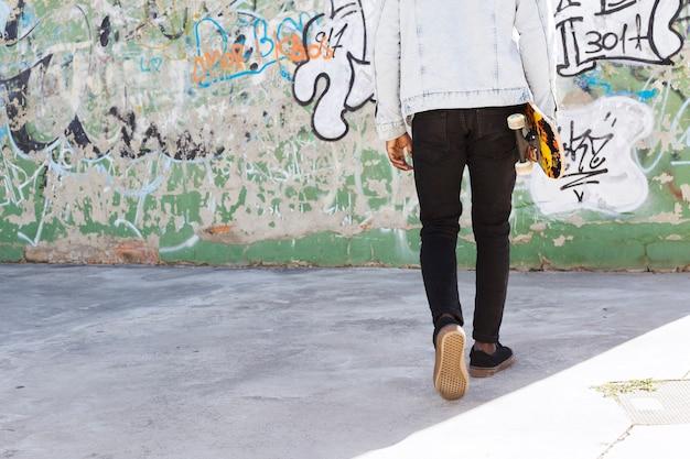 Homme avec skateboard en milieu urbain Photo gratuit