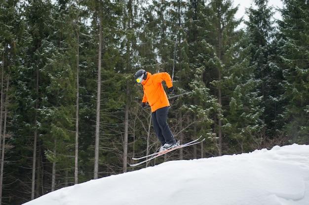 Homme de skieur volant au saut de la pente des montagnes Photo Premium
