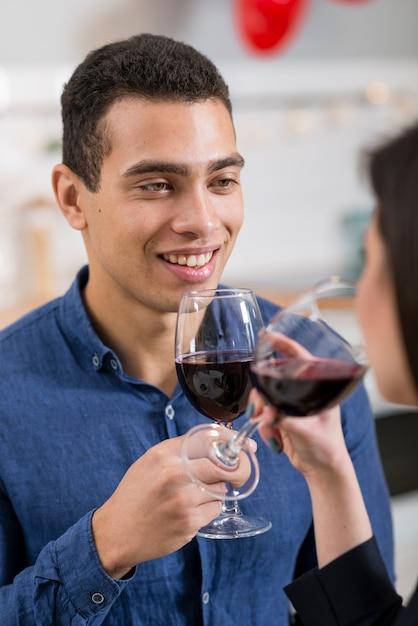 Homme Smiley Regardant Sa Petite Amie Tout En Tenant Un Verre De Vin Photo gratuit