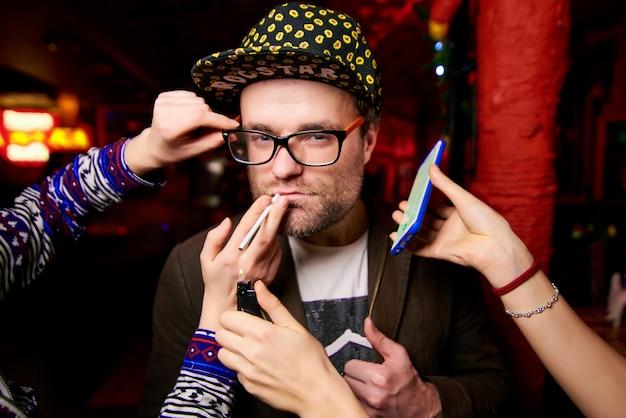 Homme avec des soies dans un bonnet jaune près duquel les mains des femmes tiennent une cigarette, un briquet et un téléphone Photo Premium