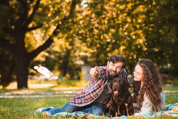 Homme avec son chien et sa petite amie montrant quelque chose dans le parc Photo gratuit