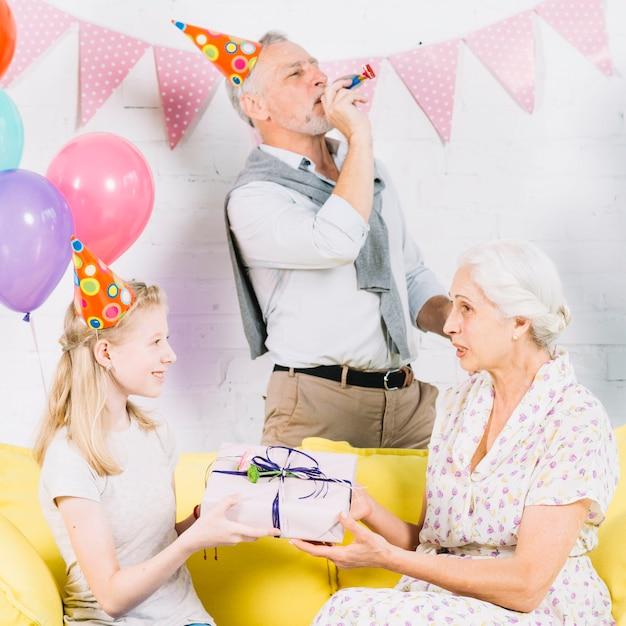 Homme souffle corne de fête tandis que la fille donne un cadeau d'anniversaire à sa grand-mère Photo gratuit