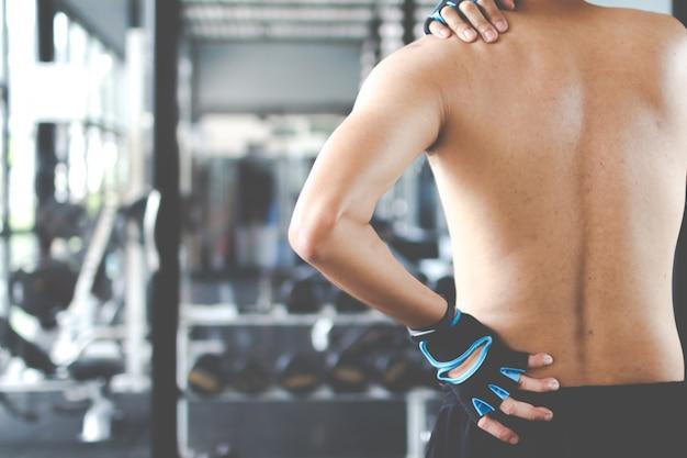 Homme Souffrant De Douleurs Au Cou Et Au Dos, Massage Du Corps Masculin, Douleur Dans Le Corps De L'homme Dans La Salle De Gym. Photo Premium
