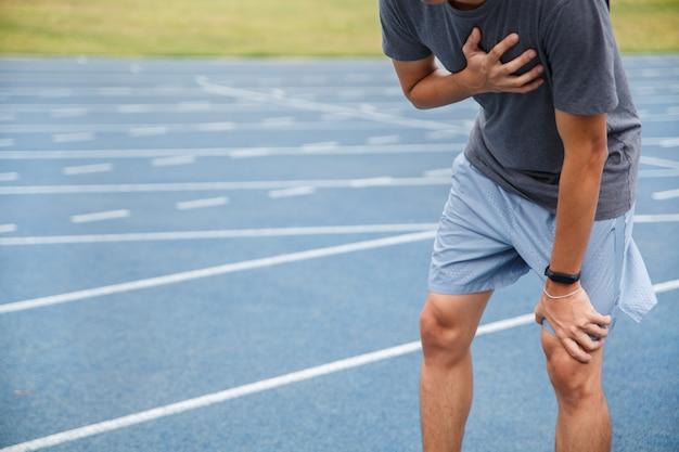 Homme souffrant de douleurs à la poitrine ou de symptômes de cardiopathie en courant sur la piste de course bleue en caoutchouc. Photo Premium