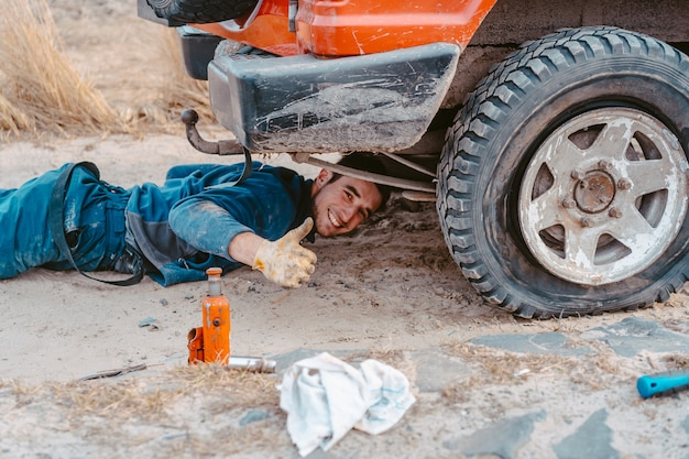 L'homme Soulève Sur Un Camion 4x4 Jack Hors Route Photo gratuit