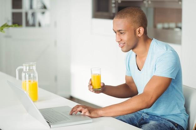 Homme souriant à l'aide d'un ordinateur portable et buvant du jus d'orange dans le four Photo Premium